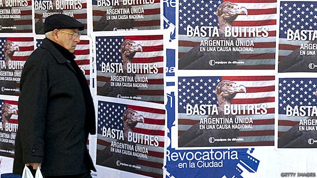 Un hombre en Argentina pasa frente a una pancarta de protesta contra los fondos buitre