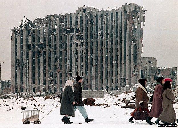 格罗兹尼市民经过被炸毁的总统府