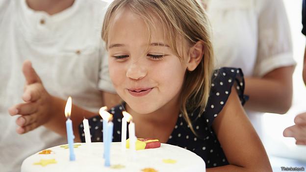 Девочка задувает свечки на торте