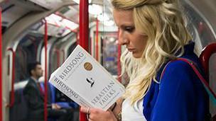 Девушка читает в метро