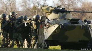 Presuntos soldados rusos tras un vehículo blindado en Belbek, Crimea