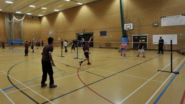 Students playing badminton in a sports hall