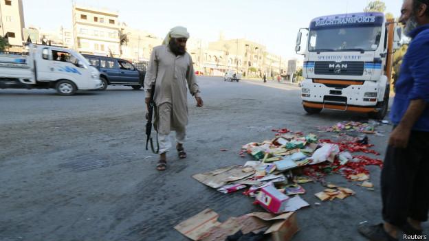 Guardia de Estado Islámico vigila mientras se descartan productos supuestamente en malas condiciones en Raqqa