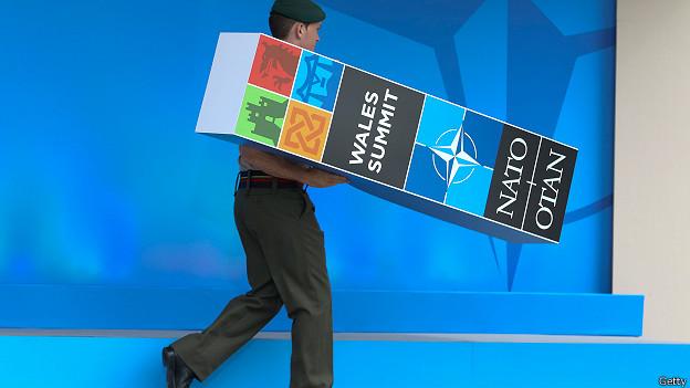 Военнослужащий НАТО убирает сцену после саммита в Уэльсе