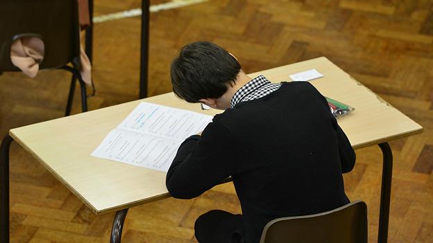 Ученик за столом сдает экзамен