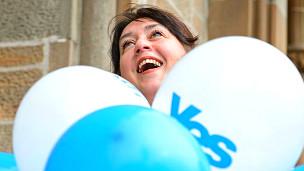 """Mujer en Escocia con un globo que dice """"Sí"""" en alusión al referendo del jueves"""