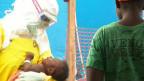 Trabajadores de la salud con un traje de protección contra el ébola