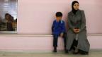 Niño con su madre en una escuela de Damasco