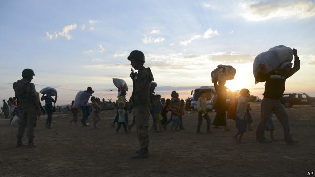 Soldados turcos guardam fronteira com a síria enquanto refugiados sírios atravessam | Foto: AP