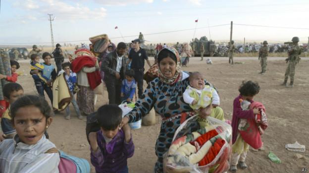 Refugiados sírios atravessam fronteira com a Turquia   Foto: AP