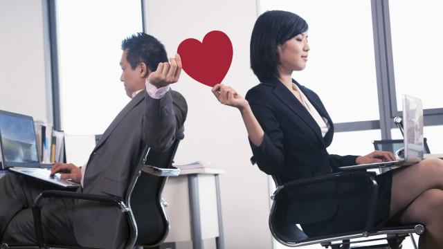 Dos personas pasándose un corazón de papel