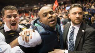 Un activista es sacado por la fuerza en Chicago durante un discurso de Trump.