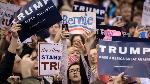 Seguidores de Trump sostienen carteles durante su presentación en Ohio.