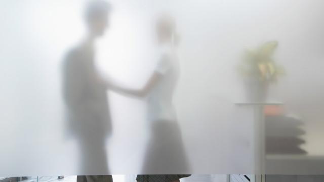 Dos personas en actitud romántica tras una pared de vidrio
